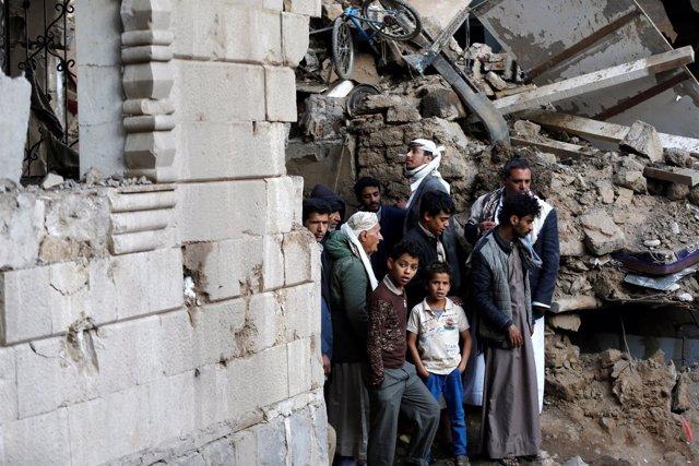 Varias personas junto a un edificio bombardeado en Saná