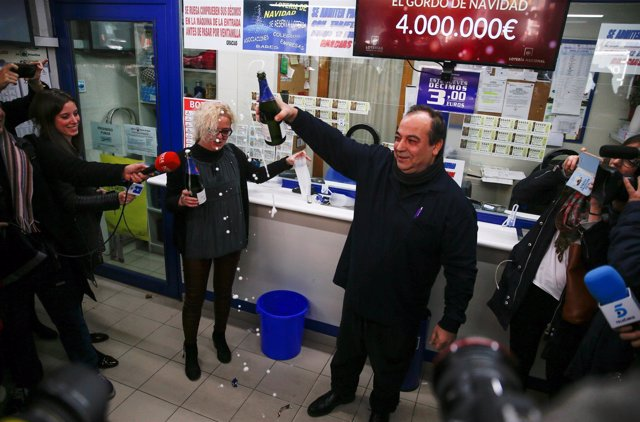 Lottery kiosk owners Agustin Ramos and his wife Maria Jose Rojo celebrate sellin