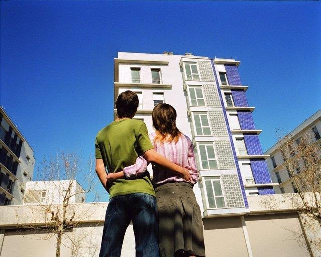 Jóvenes mirando un edificio de viviendas