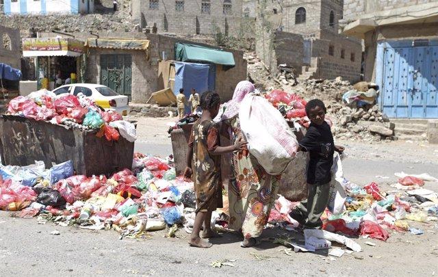 Niños yemeníes buscan comida en la basura en un suburbio de Saná