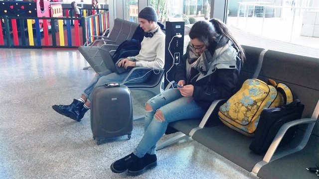 Dos turistas pasajeros aeropuerto carga móviles USB telefonos enchufes espera