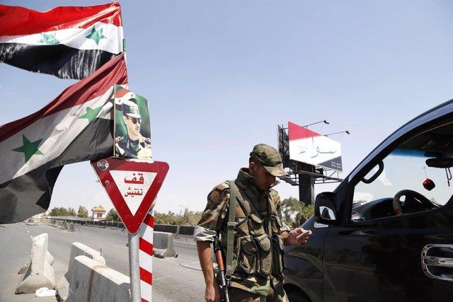 Soldado en un control en una carretera de Damasco
