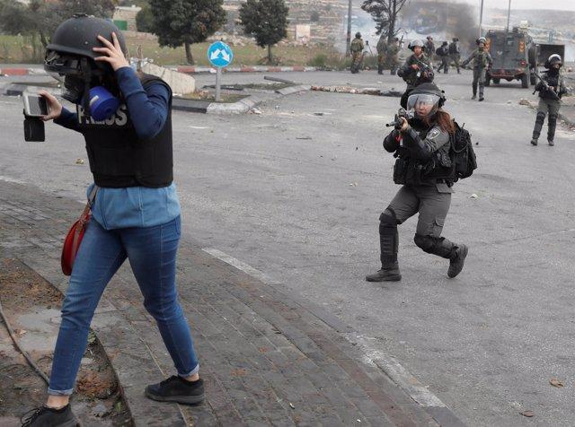 Una policía israelí apunta a un periodista
