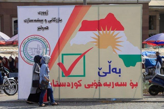 Mujeres iraquíes caminan por la calle cerca de las pancartas del referéndum del