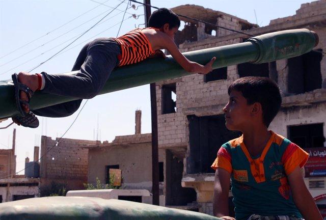 Niños jugando con restos de armamento en Deraa