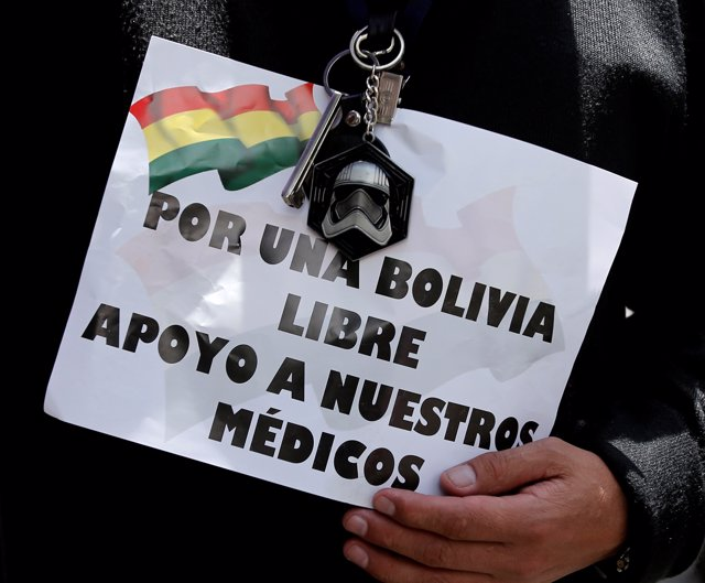 "A demonstrator holds a sign that reads "" For a free Bolivia, I support our docto"