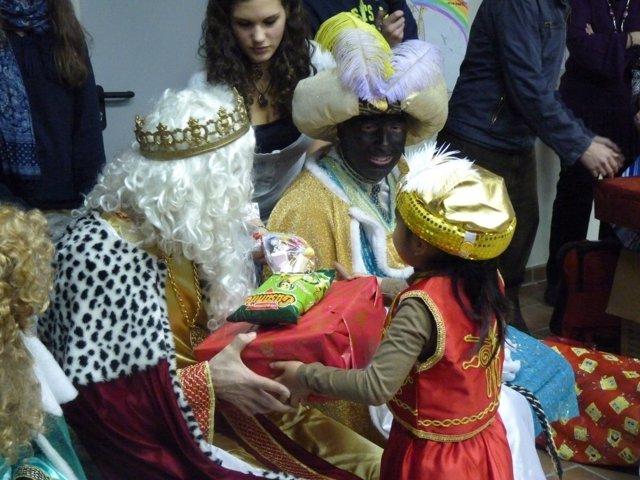 Una niña recibe su regalo de Reyes de manos del Rey Melchor