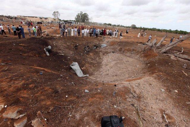 Personas junto a un cráter causado por una explosión en Garabulli