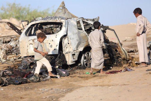 Niños yemeníes junto a los restos de un coche alcanzado por un ataque aéreo