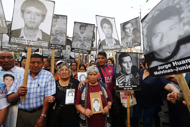 People holding pictures of victims of the guerrilla conflict in the 80s and 90s