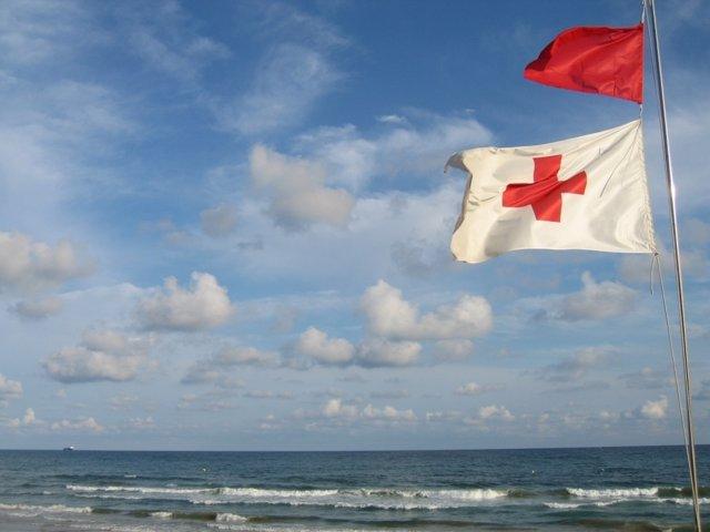 Una bandera de Cruz Roja ondea al viento