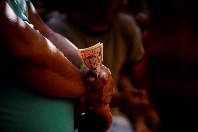 Un cubano sostiene un fajo de billetes