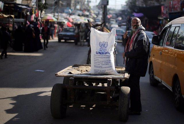 Un palestino junto a un saco de harina de la UNRWA en la Franja de Gaza
