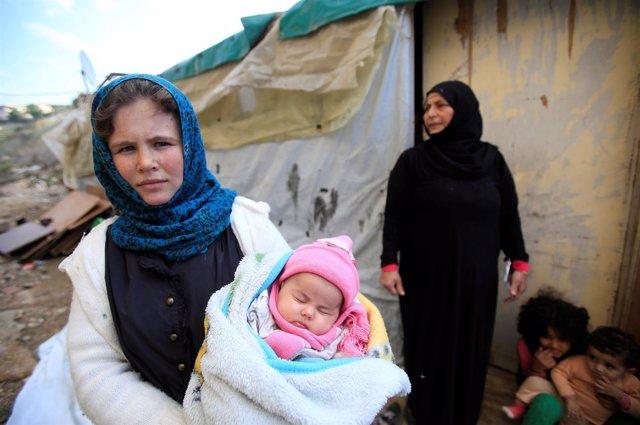 Una refugiada siria sostiene a un niño en el sur del Líbano