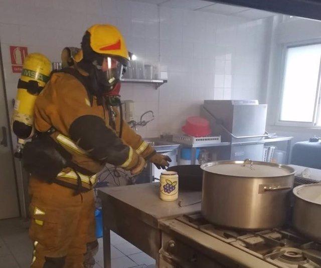 Uno de los bomberos desplazados en la cocina del centro Maigmó