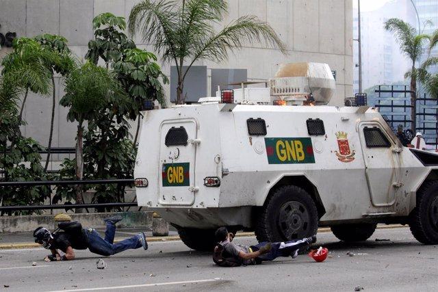 Manifestantes en suelo tras ser golpeados por un vehículo blindado en Caracas