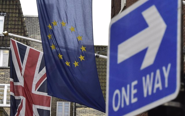 Bandera de Reino Unido y la UE junto a señal de 'one way'