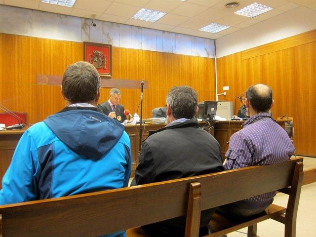 Los tres acusados, de espaldas, durante el juicio.