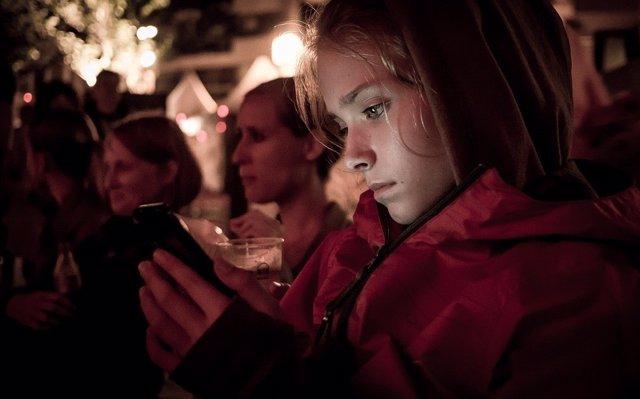 Niña usando un smartphone en una celebración