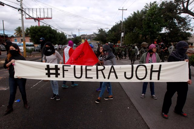 Demonstrators hold a banner during a protest against the re-election of Honduras