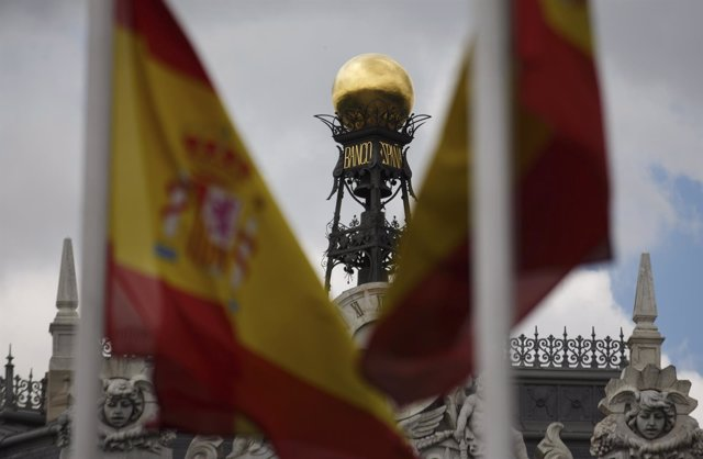 The dome of the Bank of Spain is seen between Spanish flags in central Madrid Ju