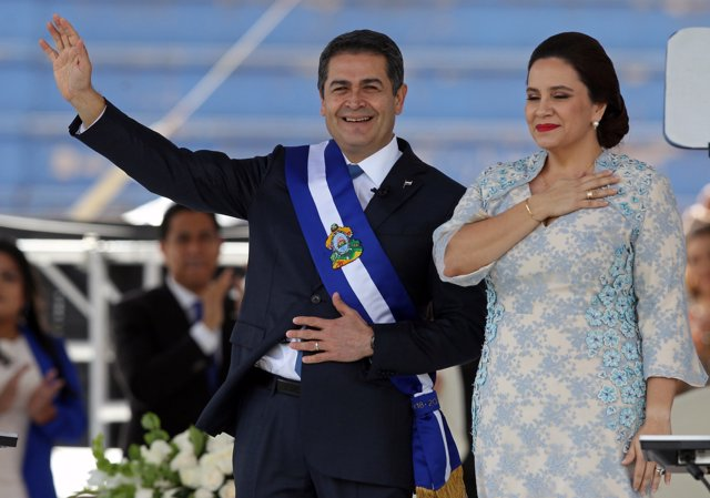 Honduran President Juan Orlando Hernandez waves beside his wife, Ana Garcia de H