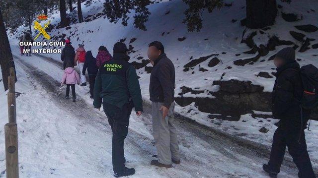 Los rescatados caminan hacía los coches 4x4 de la Guardia Civil