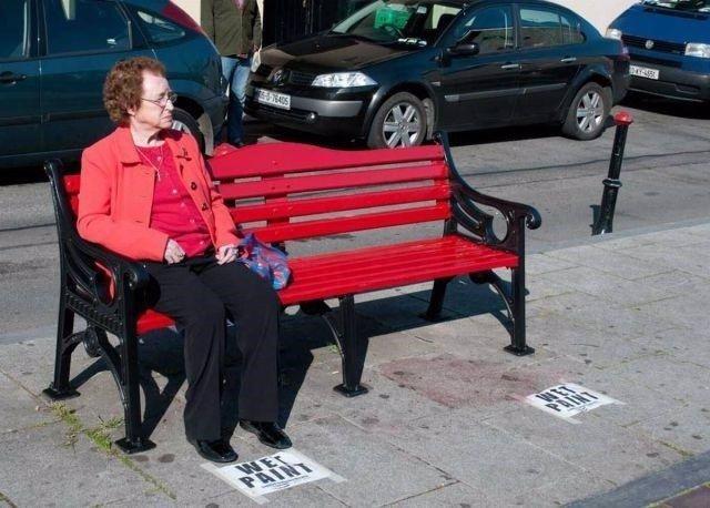 Una señora está sentada en un banco recién pintado y no se ha dado cuenta