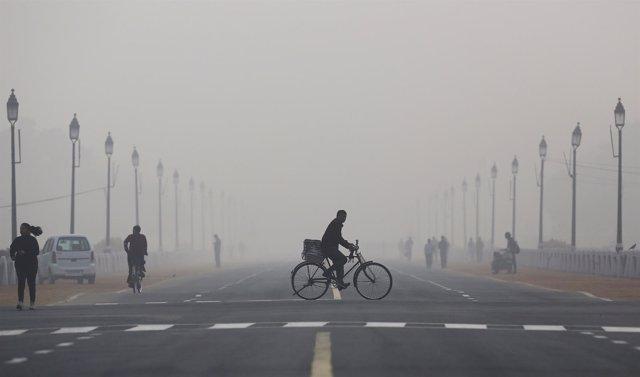 Hombre en bicicleta en Nueva Delhi en medio de la contaminación