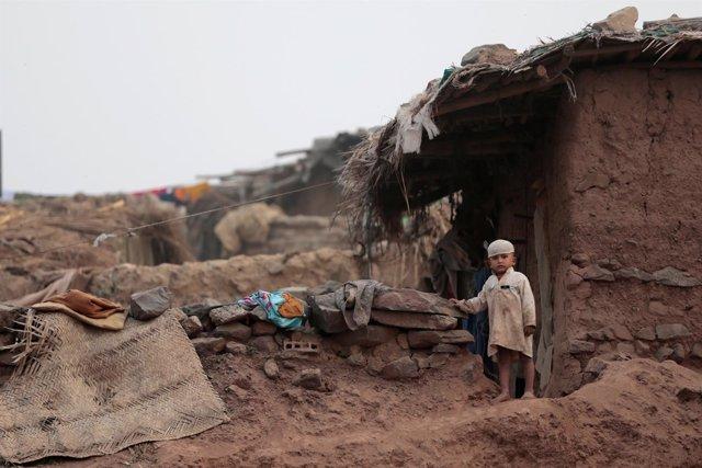 Un niño frente a la casa de su familia en un campo de refugiados afganos en Isla