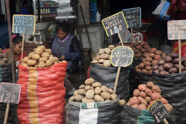 Una mujer vende patatas en el distrito de La Victoria, en Lima.