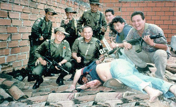 Policia posando junto al fallecido Pablo Escobar