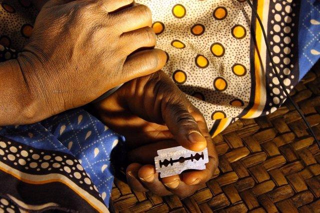 Una mujer se dispone a practicar la mutilación genital femenina en Kenia