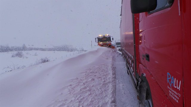 Camiones en la carretera con nieve en Cantabria. Temporal. Tráfico cortado.