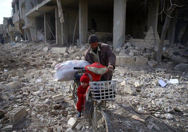 Un hombre con su hija en una bici en una zona bombardeada en Ghuta Oriental
