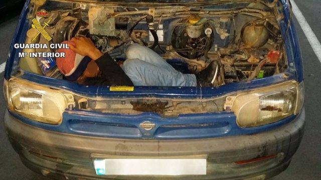 Inmigrante oculto en el hueco del motor de un coche