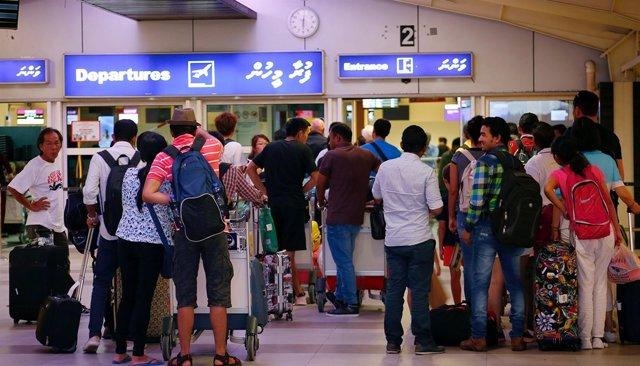 Decenas de turistas esperan en el aeropuerto internacional de Velana