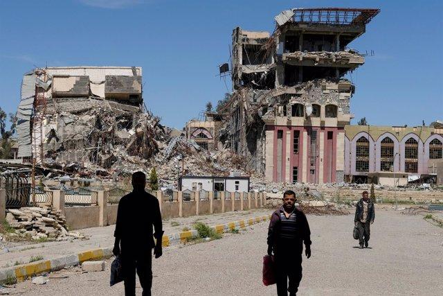 Personas frente a los restos de la Universidad de Mosul