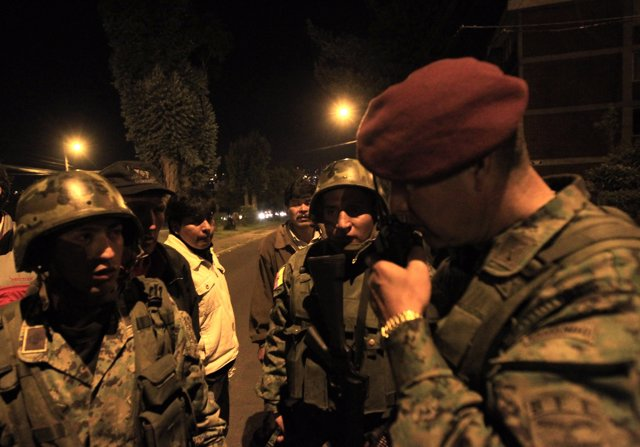 Army soldiers consult with their commanders as they clash with striking police o