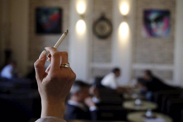 Una mujer sostiene un cigarrillo en una cafetería de Viena