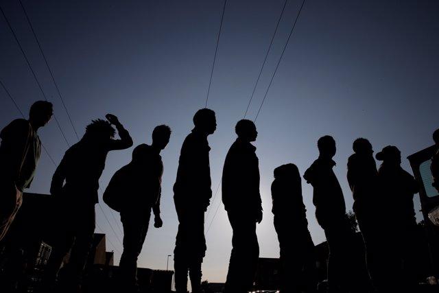 Migrantes hacen cola cerca de Calais