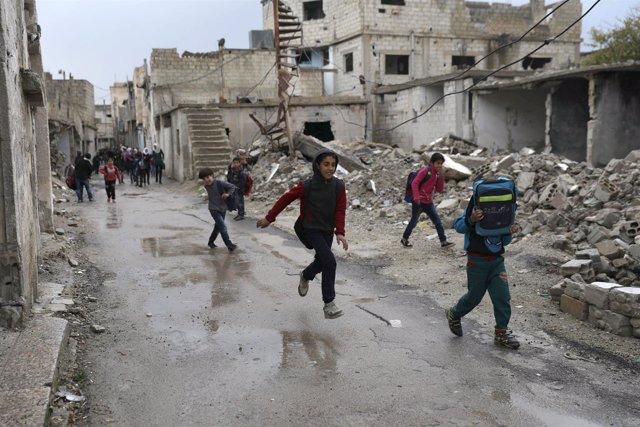 Niños junto a edificios destruidos en Deraa