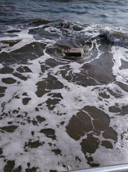 Imagen del bulto flotando en la orilla.