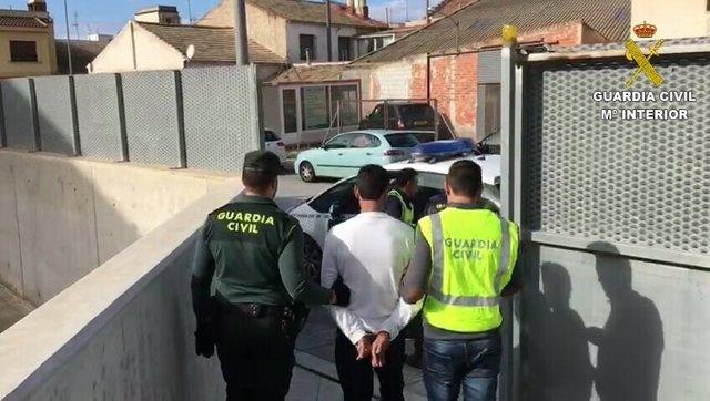 El detenido, custodiado por dos agentes