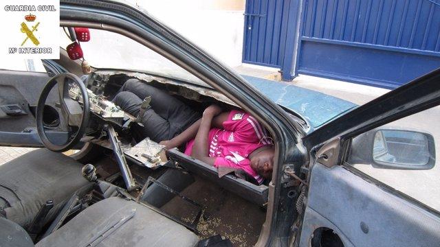 Inmigrante en el salpicadero de un coche en Melilla.