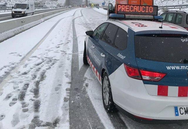 Coche de los Mossos d'Esquadra en una carretera con nieve
