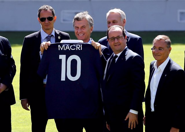 Argentina's President Mauricio Macri holds up a French soccer jersey with his na