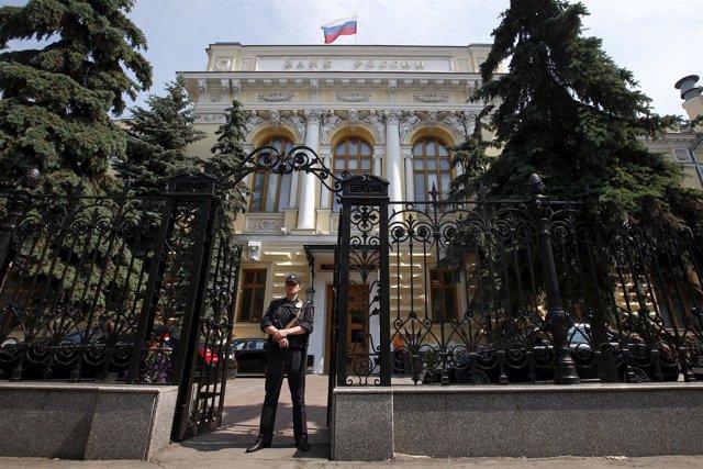Un policía vigila la entrada principal del Banco de Rusia en Moscú