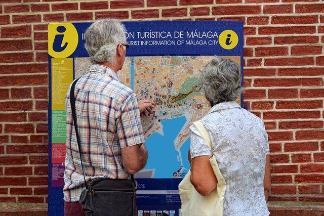 Turistas mirando un callejero de Málaga.
