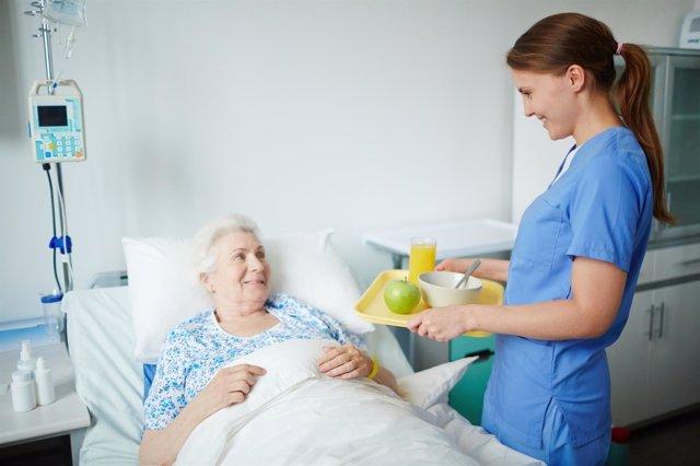 Disfagia. Enfermera lleva comida a una paciente